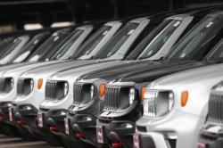 In this Sunday, April 26, 2020, photograph, a long row of unsold 2020 Renegades sits at a Chrysler/Jeep dealership in Englewood, Colo.