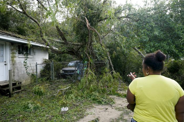 Seleka Souls looks over a neighbor's home that was damaged by Hurricane Sally, Friday, Sept. 18, 2020, in Pensacola, Fla. (AP Photo/Gerald Herbert)