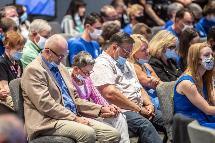 In this file photo from Sept. 9, 2020, people attending an event with Vice President Mike Pence, pray before he took the stage to speak