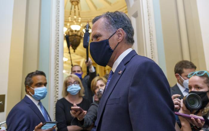 Sen. Mitt Romney, R-Utah, leaves the Senate Chamber following a vote, at the Capitol in Washington.