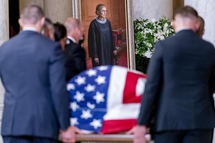 The flag-draped casket of Justice Ruth Bader Ginsburg, carried by Supreme Court police officers, arrives in the Great Hall at the Supreme Court in Washington.