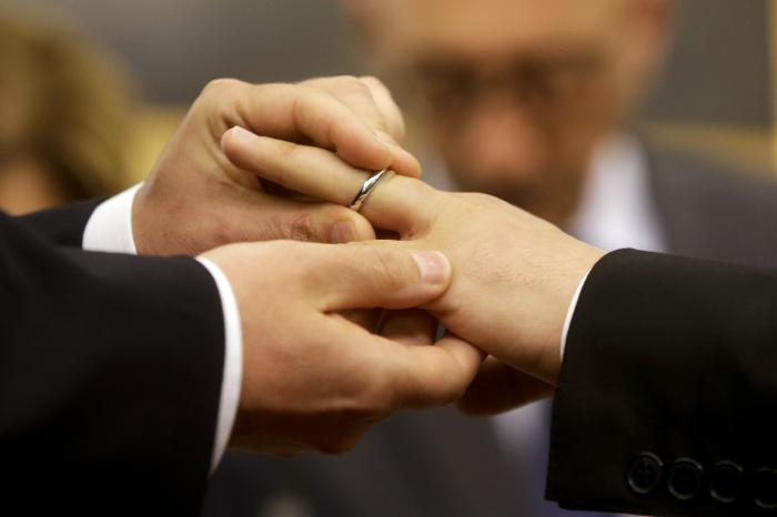 Mauro Cioffari, left, puts a wedding ring on his partner Davide Conti's finger as their civil union is being registered by a municipality officer during a ceremony in Rome's Campidoglio Capitol Hill.