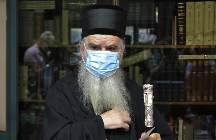 Bishop Amfilohije wearing a mask against the spread of COVID-19, prepares to vote in parliamentary elections at a polling station in Cetinje.