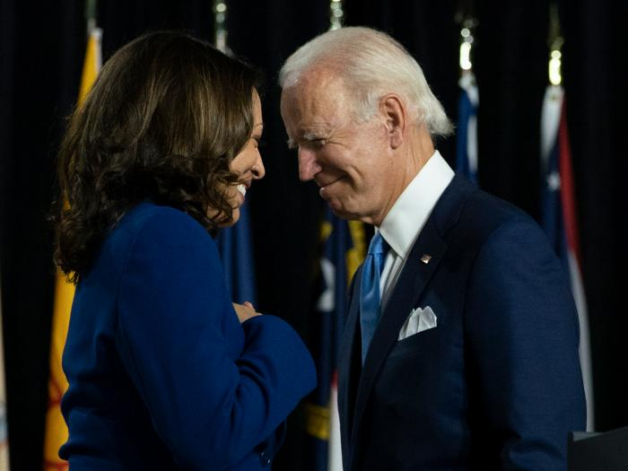 In this Aug. 12, 2020, file photo, Democratic presidential candidate former Vice President Joe Biden and his running mate Sen. Kamala Harris, D-Calif., pass each other as Harris moves to the podium to speak during a campaign event at Alexis Dupont High School in Wilmington, Del.