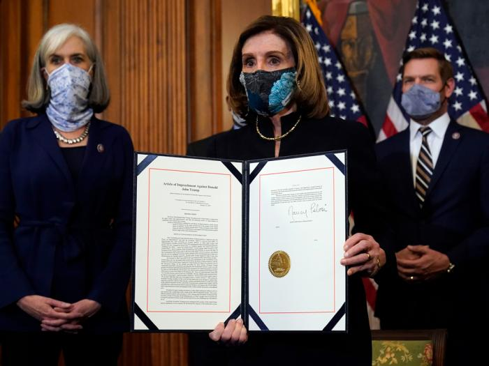 House Speaker Nancy Pelosi of Calif., displays the signed article of impeachment against President Donald Trump in an engrossment ceremony before transmission to the Senate for trial on Capitol Hill, in Washington, Wednesday, Jan. 13, 2021
