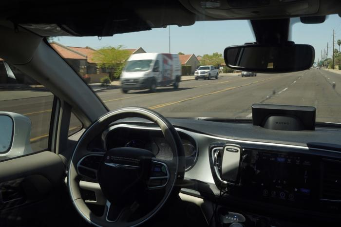 In this April 7, 2021 file photo, a Waymo minivan moves along a city street as an empty driver's seat and a moving steering wheel drive passengers during an autonomous vehicle ride in Chandler, Ariz.